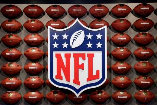 The NFL Logo in front of a case full of each teams official football
