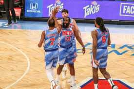 Photo of four Nets players high fiving while walking off the court. From left to right: #7 Kevin Durant, #13 James Harden, #12 Joe Harris, and #6 Deandre Jordan.
