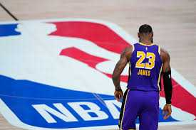 Lakers star #23 Lebron James stands over the NBA logo.