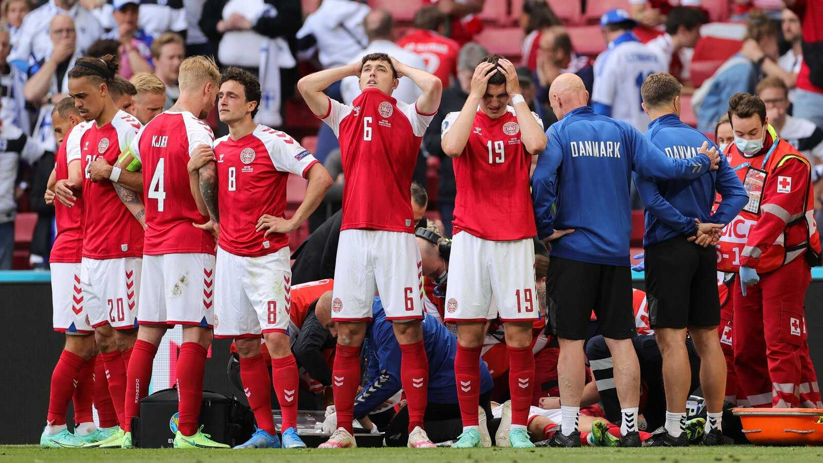 Christian Eriksen is tended to as his Denmark teammates create a ring around him to shield him from view.