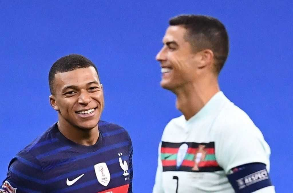 Cristiano Ronaldo and Kylian Mbappé laughing together during Euro 2020.