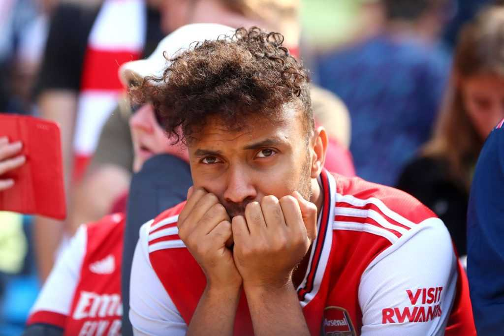 An Arsenal fan is upset as the team loses another game.