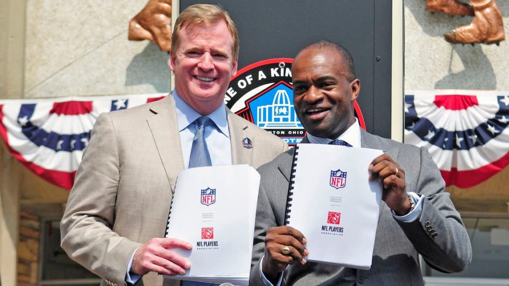 """NFL commissioner Roger Goodell and NFLPA executive director DeMaurice Smiths holding the current CBA. """"pictured here"""""""